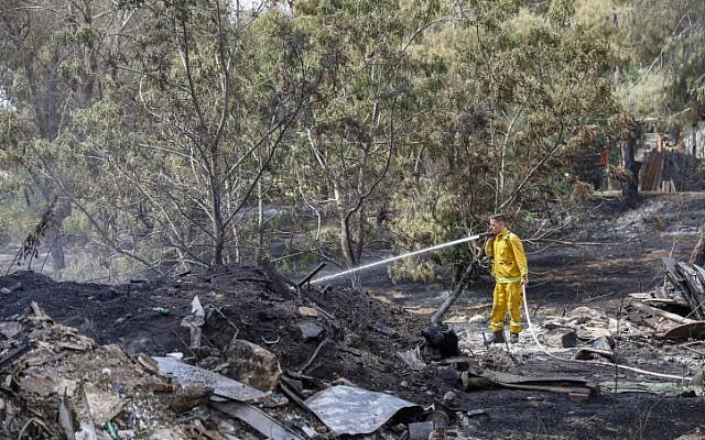 Firefighters extinguish the remains of a fire in Kibbutz Harel, on May 24, 2019. (Noam Revkin Fenton/Flash90)