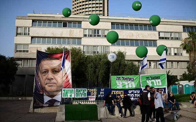 Israeli protesters holding up Meretz signs, and a photo of Turkey's Recep Tayyip Erdogan, take part in a demonstration outside the Tel Aviv Museum on May 25, 2019. (Tomer Neuberg/Flash90)