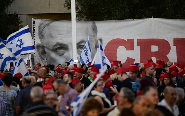 Israelis wear a Turkish fez as they take part in a demonstration against Israeli Prime Minister Benjamin Netanyahu outside the Tel Aviv Museum on May 25, 2019. (Tomer Neuberg/Flash90)