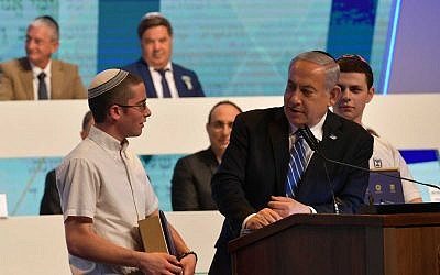Prime Minister Benjamin Netanyahu, right, speaks to International Bible Quiz for Youth winner Yonatan Weisman of Jerusalem, left, on Israel's Independence Day, May 9, 2019. (Kobi Gideon/GPO)