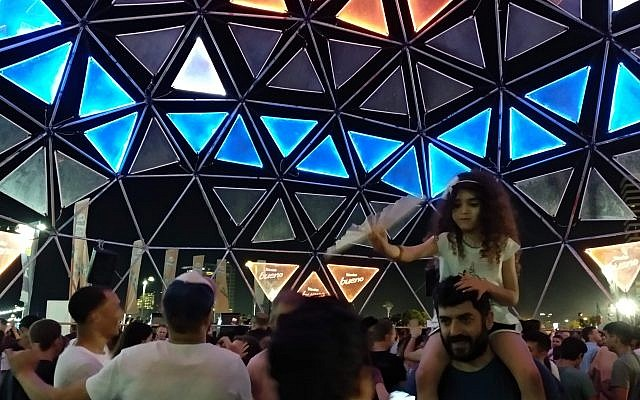 People dance in one of the many DJ spots at the Eurovision Village in Tel Aviv's Charles Clore Park on May 16, 2019. (Melanie Lidman/Times of Israel)