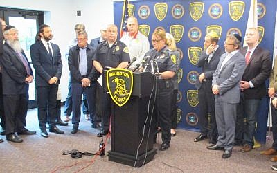 Julie Flaherty, acting police chief of Arlington, Mass., addresses a news conference at the town's police station as Rabbi Avi Bukiet, second from left, looks on, May 17, 2019. (Penny Schwartz)