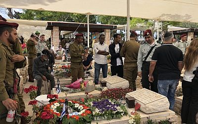 Bereaved family members stand in front of their loved one's grave at Ashkelon's military cemetery on Memorial Day, May 8, 2019. (Jacob Magid/Times of Israel)
