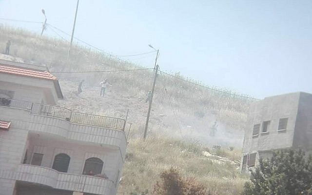 A photo from the Yesh Din rights group shows what it says are Israeli settlers by a fire they started near the northern West Bank village of Asira al-Qibliya on May 17, 2019. (Yesh Din)