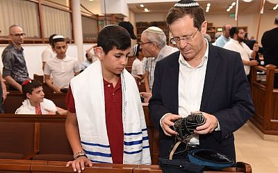 Jewish Agency head Isaac Herzog helps a participant in a bar and bat mitzvah for deaf teens to unwrap his tefillin at the Nitzanim Synagogue in Jerusalem on May 20, 2019. (Nachshon Philipson)