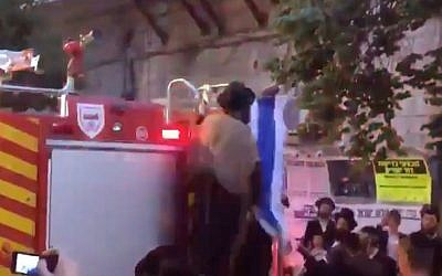 A screenshot from video of an ultra-Orthodox man in Jerusalem's Mea Shearim neighborhood ripping an Israeli flag off a fire truck on May 9, 2019. (Screen capture: Twitter)