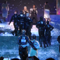 "Madonna and Quavo sing ""Future"" at the Eurovision Song Contest as two dancers walk arm-in-arm with Israeli and Palestinian flags on their backs, May 18, 2019 (YouTube screenshot)"