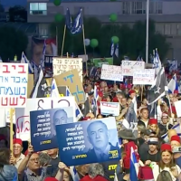 Demonstrators at a pro-democracy rally in Tel Aviv on May 25, 2019, focused on Prime Minister Benjamin Netanyahu's efforts to advance legislation to avoid prosecution in three criminal cases he faces. Some protesters wear Turkish-style Fez headgear, to warn against Israel turning into a Turkey-style regime (Channel 13 screenshot)