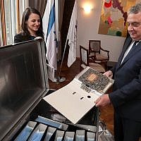 Israel's ambassador in Germany, Jeremy Issacharoff, right, holds documents prior to a handing over ceremony at the embassy of Israel in Berlin, Germany, Tuesday, May 21, 2019. German authorities are handing over to Israel some 5,000 documents kept by a confidant of Franz Kafka, a trove whose plight could have been plucked from one of the author's surreal stories. (AP Photo/Michael Sohn)