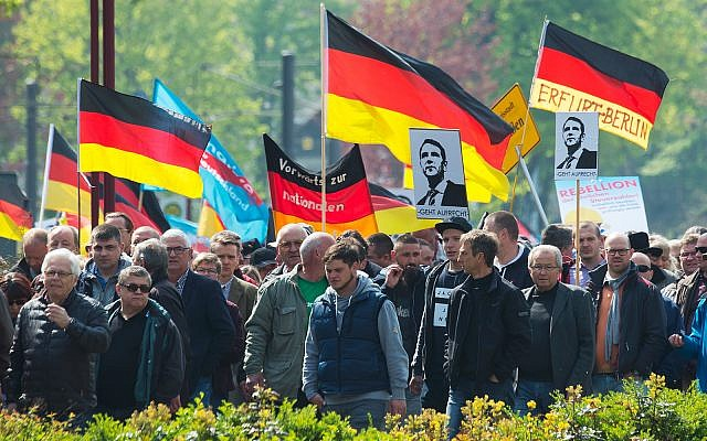 People hold flags during a demonstration by Germany's nationalist party AfD (Alternative for Germany) on May Day in Erfurt, central Germany, May 1, 2017. (AP Photo/Jens Meyer)