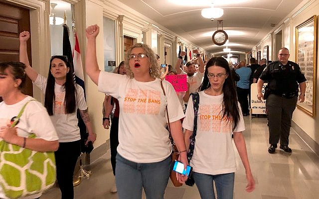Protesters march through the halls of the Missouri Capitol outside the House chamber on May 17, 2019, in Jefferson City, Missouri, in opposition to legislation prohibiting abortions at eight weeks of pregnancy. (AP Photo/David A. Lieb)