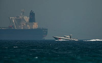 "An Emirati coast guard vessel passes an oil tanker off the coast of Fujairah, United Arab Emirates, May 13, 2019. Saudi Arabia said two of its oil tankers were sabotaged off the coast of the United Arab Emirates near Fujairah in attacks that caused ""significant damage"" to the vessels, one of them as it was en route to pick up Saudi oil to take to the United States. (AP Photo/Jon Gambrell)"