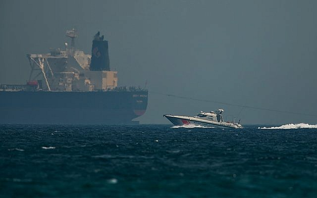 """An Emirati coast guard vessel passes an oil tanker off the coast of Fujairah, United Arab Emirates, May 13, 2019. Saudi Arabia said two of its oil tankers were sabotaged off the coast of the United Arab Emirates near Fujairah in attacks that caused """"significant damage"""" to the vessels, one of them as it was en route to pick up Saudi oil to take to the United States. (AP Photo/Jon Gambrell)"""