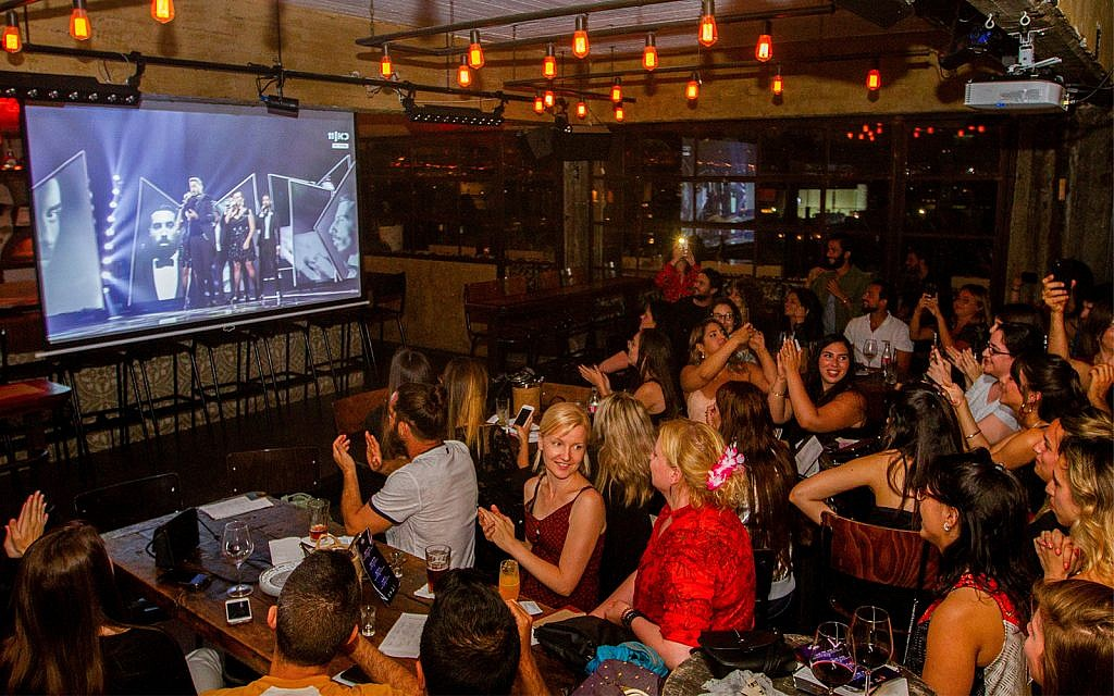 People watch the final of the 2019 Eurovision Song Contest at a pub in Tel Aviv, May 18, 2019. (Flash90)