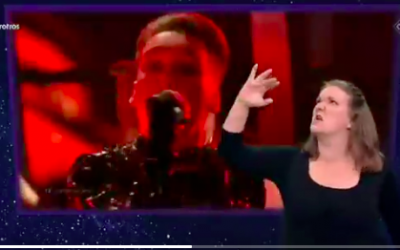 Matthías Tryggvi Haraldsson, of Iceland's Hatari, sings at the May 18 finale of Eurovision 2019, while a sign language interpreter gives a spirited translation of his vocals. (Courtesy Twitter screen grab)