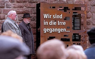 People stand around an installation during the official inauguration of a memorial in remembrance of the Institute for the Study and Elimination of Jewish Influence on German Church Life during the Third Reich in Eisenach, Germany, May 6, 2019. The words on the memorial read: 'We have gone astray'. (AP Photo/Jens Meyer)
