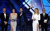 """Duncan Laurence of the Netherlands, center, celebrates after winning the 2019 Eurovision Song Contest grand final with the song """"Arcade"""" in Tel Aviv, May 18, 2019. He is flanked (from left) by the four Israeli hosts: Assi Azar, Lucy Ayoub, Bar Refaeli and Erez Tal (AP Photo/Sebastian Scheiner)"""
