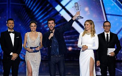 "Duncan Laurence of the Netherlands, center, celebrates after winning the 2019 Eurovision Song Contest grand final with the song ""Arcade"" in Tel Aviv, May 18, 2019. He is flanked (from left) by the four Israeli hosts: Assi Azar, Lucy Ayoub, Bar Refaeli and Erez Tal (AP Photo/Sebastian Scheiner)"