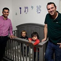 Elad Dvash-Banks, left, and his partner, Andrew, pose for photos with their twin sons, Ethan, center right, and Aiden in their apartment in Los Angeles, January 23, 2018 (AP Photo/Jae C. Hong, File)