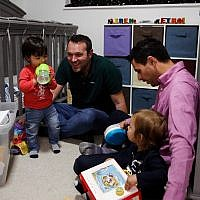 Elad Dvash-Banks, right, and his partner, Andrew, play with their twin sons, Ethan, left, and Aiden in their Los Angeles apartment, January 23, 2018. (AP Photo/Jae C. Hong)