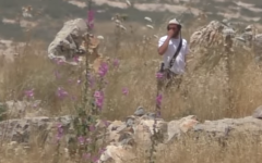 An off duty soldier stands in a Palestinian field in the northern West Bank moments before bending down and lighting brushes on fire. (Screen capture/YouTube)