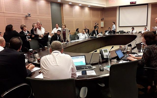 Ushers, at left, escort MK Mickey Levy (Blue and White) out of a Knesset committee debate on a bill to remove limits on the number of cabinet ministers that can be appointed by a government, May 21, 2019. (Knesset Spokesperson's Office)