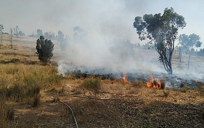 Firefighters work to extinguish a blaze in the Eshkol region of southern Israel that was sparked by a balloon-borne incendiary device from the Gaza Strip on May 22, 2019. (Eli Cohen/Fire and Rescue Services)