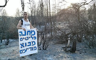 "A resident stands next to burned grounds in Mevo Modi'im holds a sing that reads ""Mevo Modiim Refugee Camp"" in protest of the government's lack of support for the moshav, May 30, 2019. (courtesy Inbal Mustacchi)"