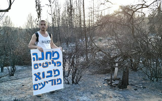 """A resident stands next to burned grounds in Mevo Modi'im holds a sing that reads """"Mevo Modiim Refugee Camp"""" in protest of the government's lack of support for the moshav, May 30, 2019. (courtesy Inbal Mustacchi)"""