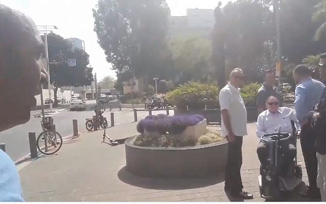 Activist Barak Cohen (L) films himself accosting Sheldon Adelson (seated) in Tel Aviv (Screencapture/Twitter)