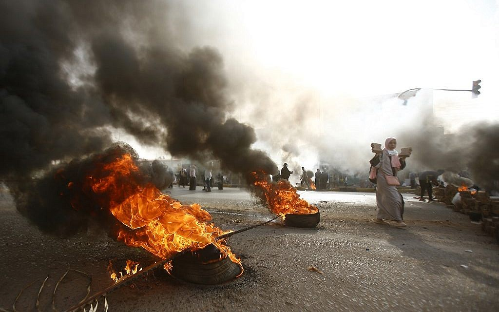A Sudanese protester walks past burning tires as military forces tried to disperse the sit-in outside Khartoum's army headquarters on June 3, 2019. (ASHRAF SHAZLY / AFP)