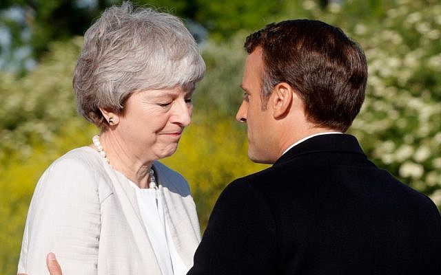 French President Emmanuel Macron greets British Prime Minister Theresa May during a ceremony to lay the first stone of the British Normandy Memorial in Ver-sur-Mer, Normandy, northwestern France, on June 6, 2019, as part of D-Day commemorations (PHILIPPE WOJAZER / POOL / AFP)