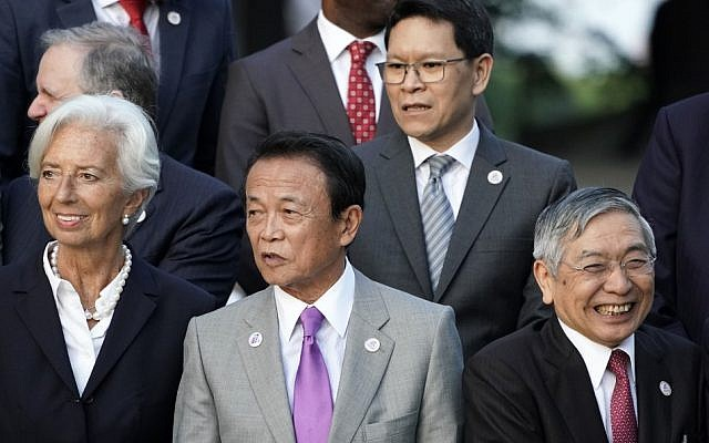 Japan's Finance Minister Taro Aso (C) stands with IMF managing director Christine Lagarde (L) and Bank of Japan governor Haruhiko Kuroda (R) before a family photo of the G20 finance ministers and central bank governors meeting in Fukuoka on June 8, 2019. (FRANCK ROBICHON / POOL / AFP)