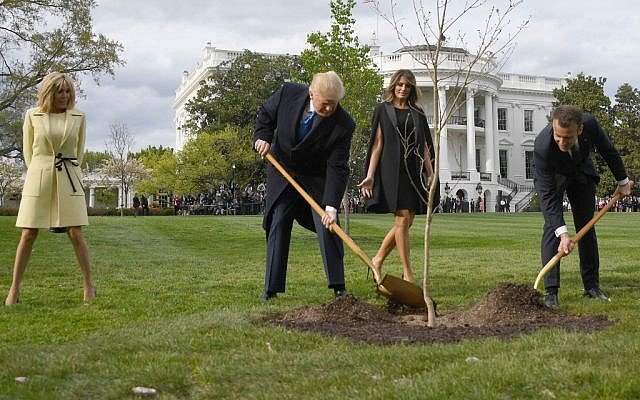 In this file photo taken on April 23, 2018 US President Donald Trump and French President Emmanuel Macron plant a tree watched by Trump's wife Melania and Macron's wife Brigitte on the grounds of the White House in Washington, DC. (JIM WATSON / AFP)