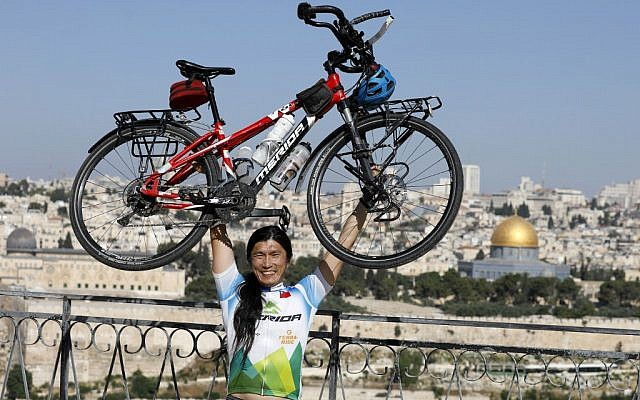 Taiwanese cyclist and world traveler Jacky Chen poses while lifting his bicycle on the Mount of Olives overlooking the Old City of Jerusalem and the Dome of the Rock on June 10, 2019. (Photo by MENAHEM KAHANA / AFP)