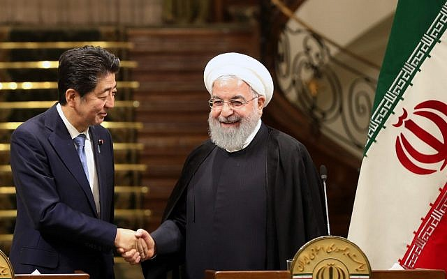 Iranian President Hassan Rouhani (R) shakes hands with Japanese Prime Minister Shinzo Abe at the Saadabad Palace in Iran's capital Tehran on June 12, 2019. (AFP)
