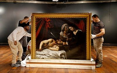 Workers unload a painting believed by some experts to be Caravaggio's 'Judith Beheading Holofernes' for its public presentation at the Drouot auction house in Paris on June 14, 2019 before it goes under the hammer on June 27 in Toulouse, the city where it was discovered five years ago. (FRANCOIS GUILLOT / AFP)
