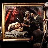 Workers hang on a wall a painting believed by some experts to be Caravaggio's 'Judith Beheading Holofernes' for its public presentation at the Drouot auction house in Paris on June 14, 2019 before it goes under the hammer on June 27 in Toulouse, the city where it was discovered five years ago. (Francois Guillot/AFP)
