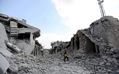 A picture taken on June 14, 2019, shows a man walking amidst the debris of destroyed buildings in the town of Ihsim, in Syria's Idlib region. (Omar Haj Kadour/AFP)