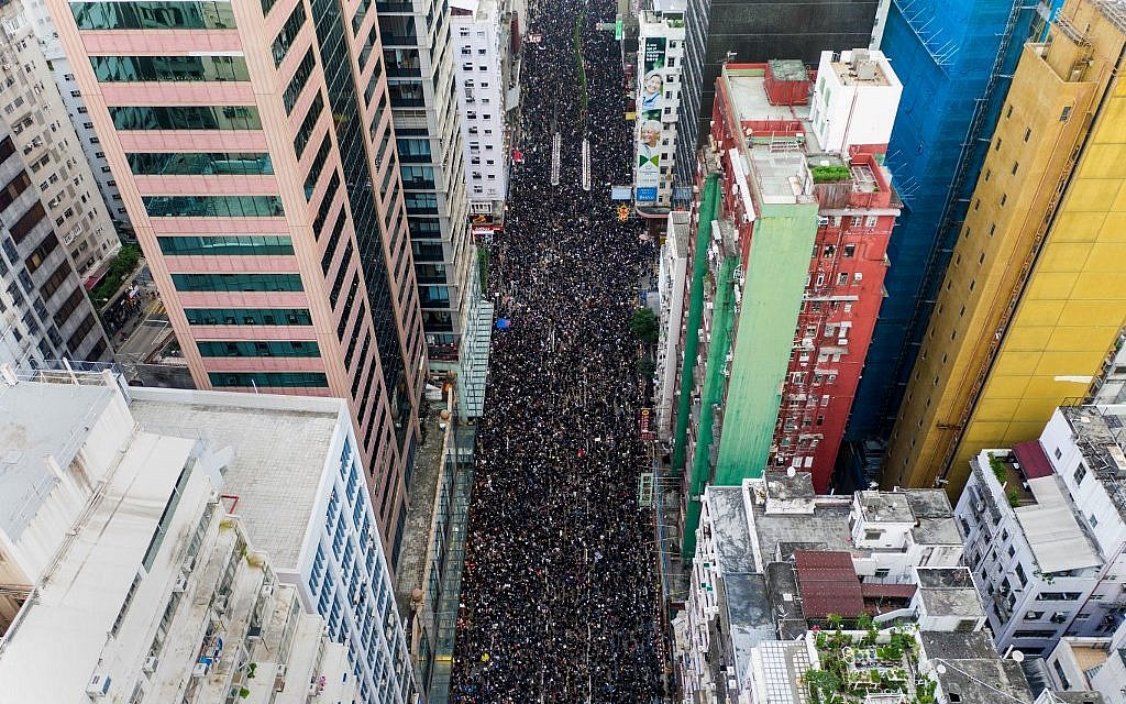 This overhead view shows thousands of protesters marching through the street as they take part in a new rally against a controversial extradition law proposal in Hong Kong on June 16, 2019. (STR / AFP)