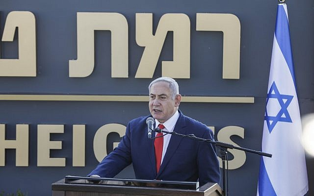 Prime Minister Benjamin Netanyahu gives a speech before the newly-unveiled sign for the new community of 'Ramat Trump', or 'Trump Heights' in English, named after the incumbent US President during an official ceremony on the Golan Heights, Israel,  June 16, 2019.  (Jalaa MAREY/AFP)