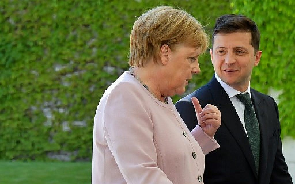 German Chancellor Angela Merkel and new Ukrainian President Volodymyr Zelensky walk to the chancellery after they inspect a military honor guard on June 18, 2019 in Berlin. (Tobias SCHWARZ / AFP)