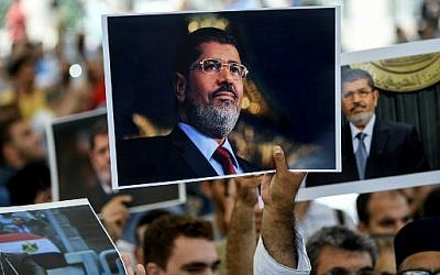 People hold a picture of the late Egyptian President Mohamed Morsi during a symbolic funeral ceremony on June 18, 2019 at Fatih mosque in Istanbul, Turkey. (AFP)