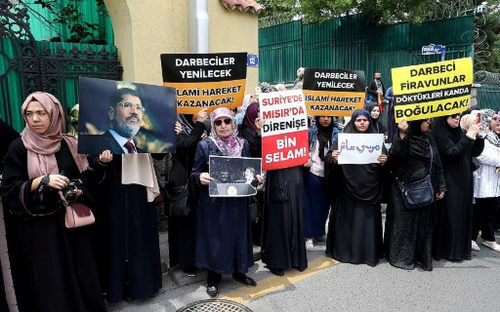 "A group of women holds  banner reads "" The putschists will be defeated, Islamic movement will win "" and "" Thousand greetings to the resistance in Syria and Egypt "" during a symbolic funeral prayer for the Egyptian President Mohamed Morsi on June 18, 2019 in front of the embassy in Ankara. (Adem ALTAN / AFP)"
