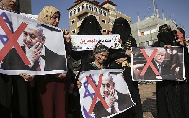Palestinian female supporters of the Islamic Jihad terror group carry posters of US President Donald Trump and Prime Minister Benjamin Netanyahu during a protest against the Bahrain economic workshop in the southern Gaza Strip town of Rafah on June 18, 2019 (SAID KHATIB / AFP)