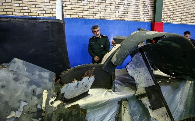General Amir Ali Hajizadeh (C), Iran's Head of the Revolutionary Guard's aerospace division, looks at debris from a downed US drone reportedly recovered within Iran's territorial waters and put on display by the Revolutionary Guard in the capital Tehran on June 21, 2019. (Meghdad Madadi / TASNIM NEWS / AFP)