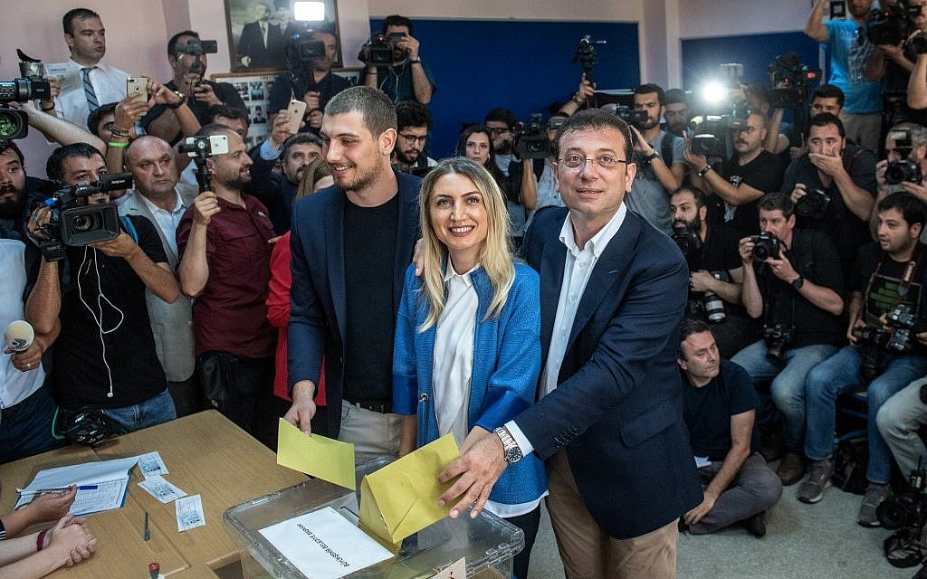 Istanbul mayoral candidate of the main opposition Republican People's Party (CHP) Ekrem Imamoglu (C-R) casts his vote with his wife Dilek Imamoglu (C-L) and their son Semih Imamoglu  on June 23, 2019 in Istanbul. (Bulent Kilic / AFP)