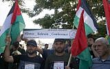 Palestinians n Gaza City on June 24, 2019, wave national flags and hold a banner denouncing the US-led Peace to Prosperity conference  in Bahrain. (MOHAMMED ABED / AFP)