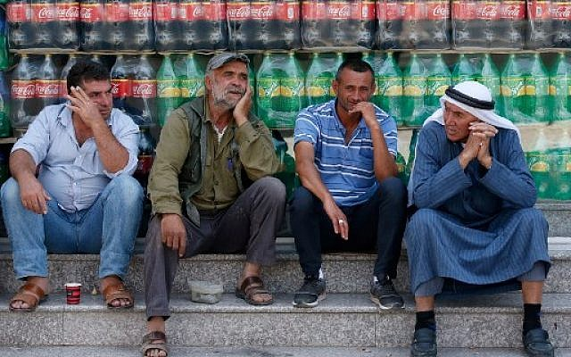 Palestinian men chat during a protest against a US-led meeting this week in Bahrain on the Palestinian-Israeli conflict, in the village of Yatta near the West Bank city of Hebron, on June 24, 2019. Finance officials were flying into Bahrain today for a US-led peace conference that holds out billions of dollars for the Palestinians, whose leaders pronounced the idea dead on arrival. The Palestinian Authority is boycotting the workshop, with prime minister Mohammad Shtayyeh criticising the plan for saying nothing about ending the Israeli occupation. (HAZEM BADER / AFP)