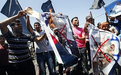 Palestinian demonstrators chant slogans behind defaced posters of Israeli Prime Minister Benjamin Netanyahu and US President Donald Trump during a protest against a US-sponsored Middle East economic conference in Bahrain, on June 26, 2019, in Khan Younis in the southern Gaza Strip. (SAID KHATIB / AFP)